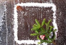 Capítulo de la nieve con un árbol de navidad y un topetón en un folleto nevoso del invierno del fondo de madera oscuro Foto de archivo