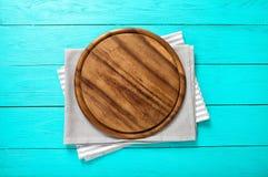 Capítulo de la tabla de cortar redonda en un mantel rayado y gris en fondo de madera azul Visión superior y lugar para el texto Imagen de archivo