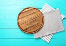 Capítulo de la tabla de cortar redonda en un mantel rayado y gris en fondo de madera azul Visión superior y lugar para el texto Fotografía de archivo libre de regalías