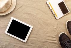Capítulo de la tableta, de la libreta y de la ropa digitales en la arena Fotos de archivo libres de regalías