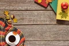 Capítulo de las hojas rojas, verdes y amarillas del otoño, de las manzanas con la taza de café o del té con los libros en fondo d foto de archivo libre de regalías