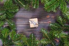 Capítulo de las ramas del pino Regalo envuelto en el papel de Kraft, adornado con la cinta y el arco en color plata Decoraciones  imágenes de archivo libres de regalías