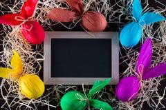 Capítulo de los huevos de Pascua en la forma de conejo con la pizarra para escribir el texto Adornamiento del día de fiesta Imagen de archivo