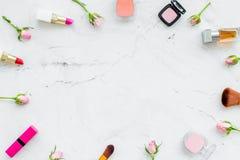 Capítulo de los productos de maquillaje rosados Barra de labios, bulto, sombreador de ojos y pequeñas flores color de rosa en la  foto de archivo libre de regalías