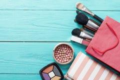 Capítulo de los productos y de los accesorios de maquillaje con el bolso rojo en fondo de madera azul Visión superior y mofa para Fotografía de archivo