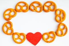 Capítulo de pretzeles y del fondo rojo del blanco del corazón Fotos de archivo libres de regalías