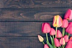 Capítulo de tulipanes en fondo de madera rústico oscuro Apenas llovido encendido