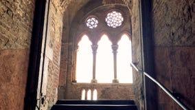 Capítulo de una escalera dentro de un castillo medieval con una ventana iluminada por el sol, Pavía almacen de video