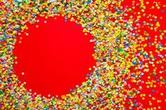 Capítulo hecho de confeti coloreado Fondo rojo Fotos de archivo