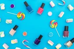 Capítulo la composición con los cosméticos femeninos y el caramelo brillante en fondo azul Visión superior Endecha plana Escritor Foto de archivo
