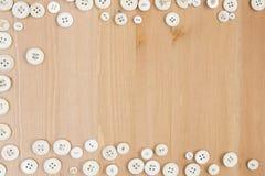 Capítulo la frontera hecha de botones viejos en fondo de madera Fotos de archivo libres de regalías