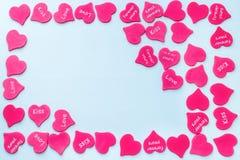 Capítulo para la tarjeta de la tarjeta del día de San Valentín con el fondo rojo dispersado de los corazones blanco fotografía de archivo