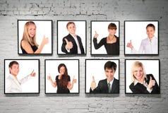 Capítulos con la gente aceptable del gesto en la pared de ladrillo blanca Fotos de archivo