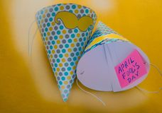 Cap, April fool`s day lettering, yellow background stock photo