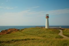 Cap aux meules lighthouse in Magdalen island. Cap aux meules lighthouse with a path and a blue sky with clouds Stock Photos
