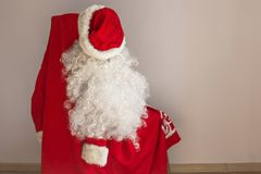 Cap, beard and Santa coat. The outfit of Santa Claus hangs on a chair. Soon the New Year, everyone can become Santa. Daylight Royalty Free Stock Image