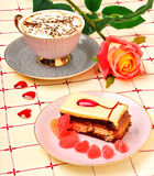 Cap of coffee, a rose and a cake on tablecloth Stock Photo