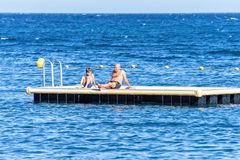 Daylight view to father and son sitting on floating swim platfor. CAP D`AIL, FRANCE - JUNE 29, 2017: Daylight view to father and son sitting on floating swim Royalty Free Stock Photography