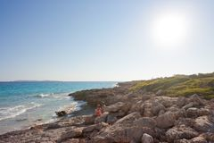 Cap de Ses Salines, Mallorca - AUGUST 2016 - Tourists sitting at. Cap de Ses Salines, Mallorca, Spain - AUGUST 2016 - Tourists sitting at the lonely beach of Ses Stock Photo