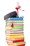 Cap and diploma on top of stack of books Royalty Free Stock Images