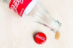 Cap, empty Coca-Cola bottle and drop of drink. MOSCOW, RUSSIA - APRIL 4, 2019: used crown cap, empty bottle from Coca-Cola beverage and drop of drink on wooden stock photography
