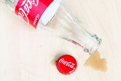 Cap, empty Coca-Cola bottle and puddle of drink. MOSCOW, RUSSIA - APRIL 4, 2019: used crown cap, empty bottle from Coca-Cola beverage and spilled puddle on stock image