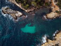 Cap falco beach in Mallorca Island. Spain. Cap falco beach with turquoise green transparent water and rocky coast, view directly from above. Aerial drone stock photos