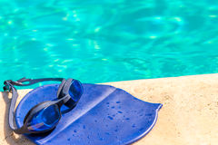 Cap and goggles on the edge of  pool Royalty Free Stock Photo