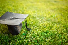 Cap graduate, lying on the lawn, green grass, can be used for ad royalty free stock photos