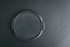 Cap lens. Black camera lens cap on the black textured table. Flat lay with copy space for text royalty free stock photo