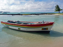 Cap Malheureux, North of Mauritius, Indian ocean. A colorful wooden boat is moored in a clear and transparent water. In the background: turquoise water, cloudy Royalty Free Stock Photography