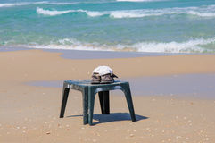 Cap and pair of shoes on a beach table Stock Photography
