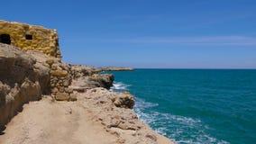 Cap rocheux près de l'océan avec les vagues et le ciel bleu clips vidéos