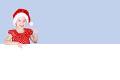 In cap Santa Claus girl shows a finger super and on advertising space Royalty Free Stock Photo