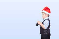 In cap of Santa Claus a little boy photographer Stock Image