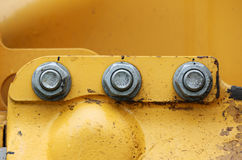 Cap screws and holes in the yellow background - on the construction equipment compactor.  Royalty Free Stock Photo