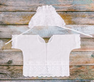 Cap and shirt for a newborn on the old rustic wooden table close-up Stock Image