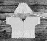 Cap and shirt for a newborn on the old rustic wooden table close-up view from above. Black and white photo Stock Photo