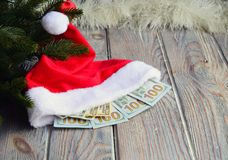 In a cap there are dollars. It is Santa`s gift. Santa`s cap is under the Christmas tree. In a cap there are dollars. It is Santa`s gift Stock Photography