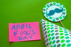 Cap, topper with mustache, April fool`s day lettering on green background royalty free stock photography