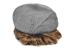 Cap and wig. A checkered flat cap over a wig for a costume on a white background Royalty Free Stock Photos