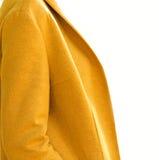 Capa amarilla de la moda en el fondo blanco foto de archivo libre de regalías