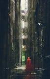 Capa con capucha roja en el callejón futurista, escena de la ciencia ficción ilustración del vector