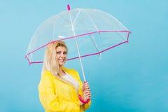 Capa de chuva vestindo da mulher feliz que guarda o guarda-chuva transparente fotos de stock