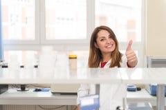 Capa de In White Lab del científico que muestra los pulgares para arriba Imágenes de archivo libres de regalías