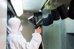 Capa del polvo de piezas de metal Un hombre en un traje protector rocía la pintura del polvo de un arma en productos de metal imagen de archivo