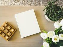 Capa do livro vazia na tabela com a decoração floral da casa da planta Imagens de Stock
