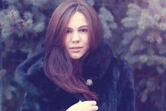 Capa morena de ojos marrones hermosa del negro del invierno de la muchacha que presenta los árboles del fondo, idea del concepto  Fotos de archivo libres de regalías