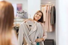 Capa que intenta de la mujer feliz en el espejo de la tienda de ropa Fotos de archivo