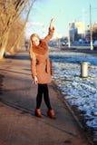 Capa que lleva que camina abajo de la calle, invierno frío DA de la mujer joven Imágenes de archivo libres de regalías